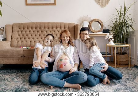 Happy Family Portrait At Home. Parents, Pregnant Mother And Father With Lovely Two Kids Sit On The C