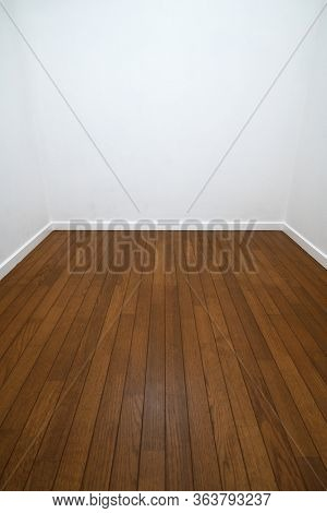 Long narrow white room. Three walls of a white room with wood flooring and white trims.