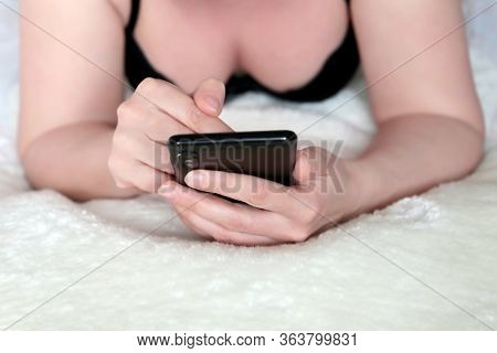 Woman In Black Bra Lying On A Bed And Using Smartphone. Mobile Phone In Female Hands, Concept Of Onl