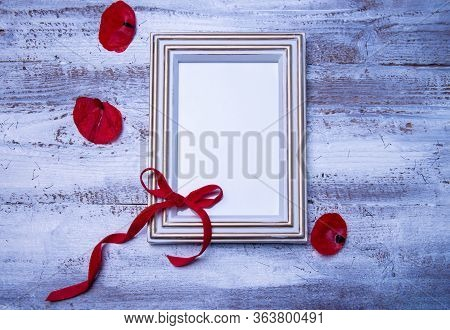 Bouquet Of Fresh Red Poppy Flowers And Empty Photoframe On Rustic Wooden Background. Floral Composit
