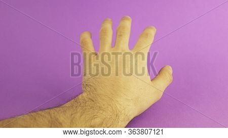 Left Male Hand In The Center On A Purple Background
