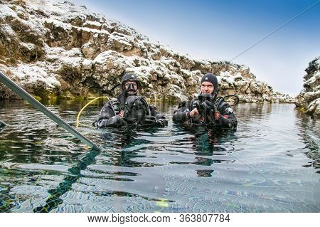 Silfra, Iceland-Feb 19, 2020: Scuba divers preparing entering in the water at Silfra rift, the place where Eurasian and the American tectonic plate are divided in Thingvellir National Park, Iceland.