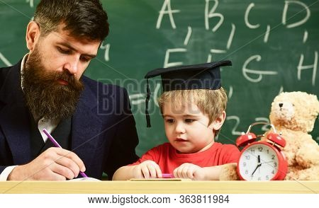 Teacher In Formal Wear And Pupil In Mortarboard In Classroom, Chalkboard On Background. Father Check