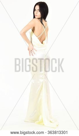 Woman In Elegant White Dress With Nude Back, White Background. Fashion Model Demonstrate Expensive F