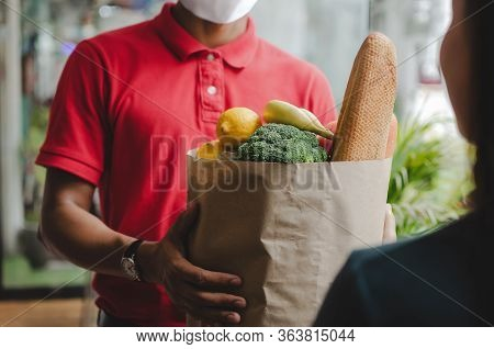 Food Delivery Service Man With Protection Face Mask In Red Uniform Holding Fresh Food Set Bag To Cus