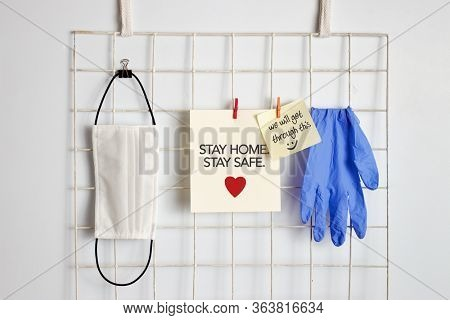 Medical mask, gloves and reminder paper note hanging on wall.