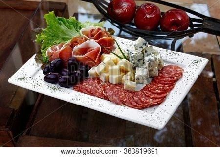 cold dish with cheese, pepperoni, olives, salad, parma ham, gorgonzola cheese