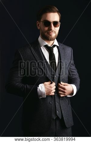 Portrait of a handsome smiling man wearing suit and sunglasses on a black background. Businessman portrait. Men's beauty, fashion. Optics for men.