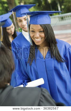 Happy graduates collecting certificate from female dean poster