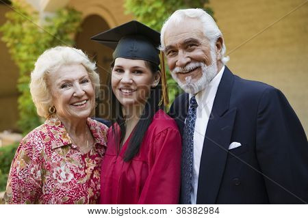 Portrait of a young female graduate with grandparents smiling