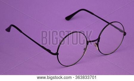 Black Round Glasses On A Purple Background