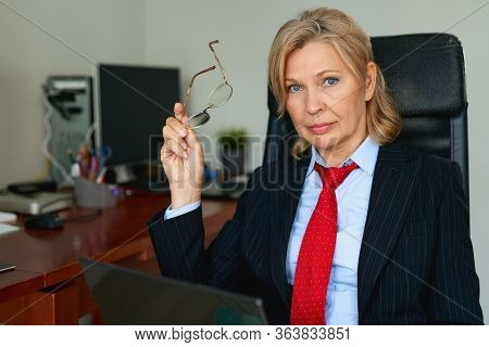 Portrait Of Mature Female Boss Working In Office Sitting In A Chair.