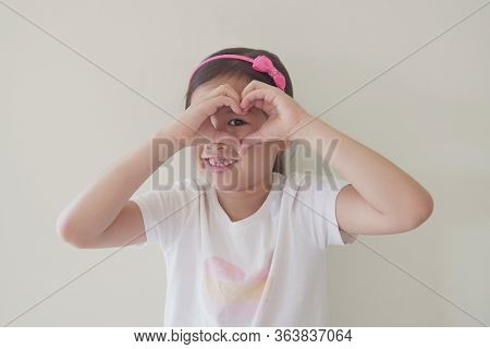 Mixed Asian Girl Making Heart Shape Hands Through Eyes, Generous, Love And Kindness, Sustainable Liv
