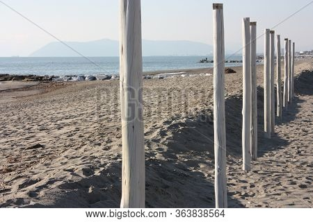 Wooden Stakes Lined Up In The Lonely Sandy Beach During The Quarantine In Versilia