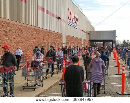 Langley, Canada - April 14, 2020. Shoppers Wait In Line At The Costco Entrance In Order To Get Into