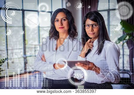 Two Serious Female Colleagues Using Tablet Pc In Restaurant. Hotel Managers In Lobby With Coronaviru