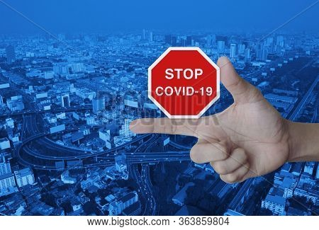 Hand Pressing Stop Covid-19 Outbreak Icon Plate Over Modern City Tower, Street, Expressway And Skysc