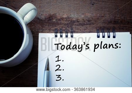 Today's Plans List With Number Written On Notebook, A Pen, And A White Cup Of Morning Coffee On A Wo
