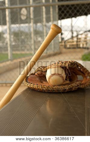 Baseball Bat and Glove on the bench of the dugout poster