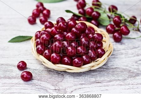 Ripe Fresh Cherries In A Wooden Bowl. Food Background. Red Juicy Cherry Berry On Grey Wooden Backgro