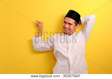 Relaxed Young Asian Muslim Man With A Blissful Smile Leaning Back Pointing A Copy Space To Presentin