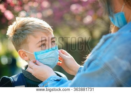 Mother Puts Her Son A Face Protective Mask Outdoors. Coronavirus, Illness, Infection, Quarantine, Me