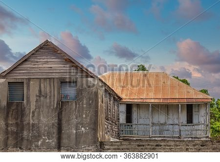 An Old Abandoned Cement Building With A Rusty Tin Roof