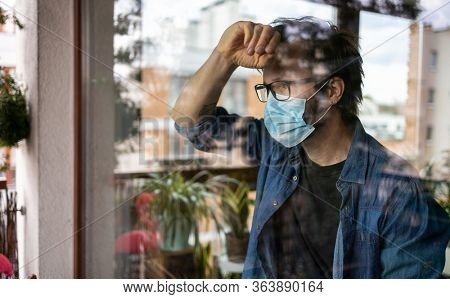 Man with face mask looking out of window