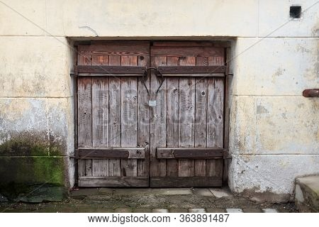 An Old Wooden Hatch On An Old Brick Wall At Tallinn, Estonia. There Is A Beautiful Old Lock On The H