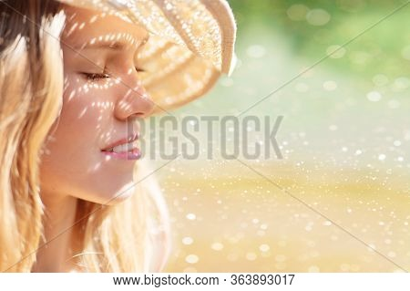 Dreaming Blonde Girl With Freckles, With Sunny Glare On Her Face. Smiling Yong Woman In A Hat On A N