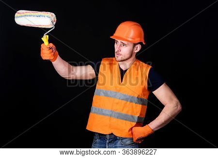 Paint And Renovate Concept. Man In Helmet, Hard Hat Holds Paint Roller, Black Background. Decorator