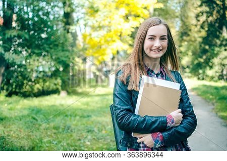 Portrait Of Smiling University Student Standing In The Park On Her Way To Class. Girl Is Wearing A B