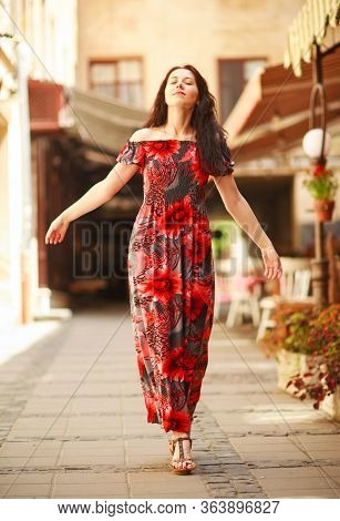 Sensual Attractive Young Woman In A Long Colorful Dress On The Street Of An Old European Town Enjoy
