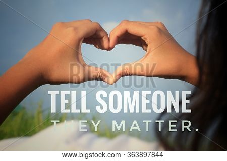 Inspirational Quote - Tell Someone They Matter. With Young Woman Making Hands Love Sign Against Blue