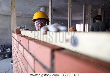 Construction Guy Helmet Measures Level Brickwork. Level Is Used When Laying Bricks In Order To Check