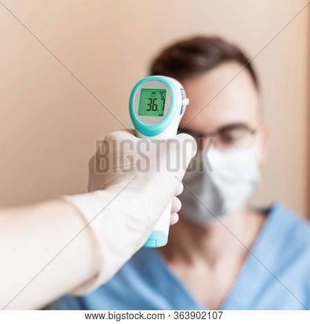 Measures The Temperature Doctor In A Medical Mask. Check For Virus Covid-19. With Security's Hand Ch