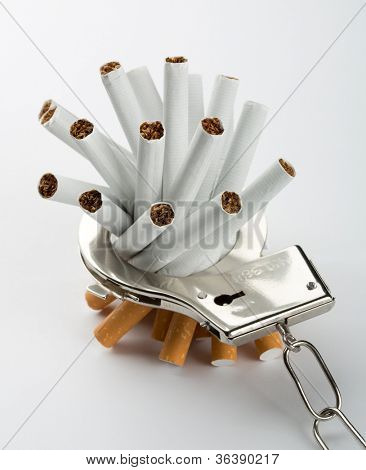 Heap of cigarettes locked to handcuffs. Closeup view