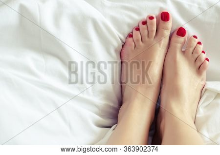 Female Feet With A Pedicure. Well Groomed Bare Feet On White Bedding, Close Up. Skin Care. Woman Bod