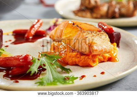 Salmon fillet with beet in herbs and passion fruit sauce close up. Seafood with beetroot slices and greenery in white plate. Delicatessen, served restaurant meal with vegetables and flavoring