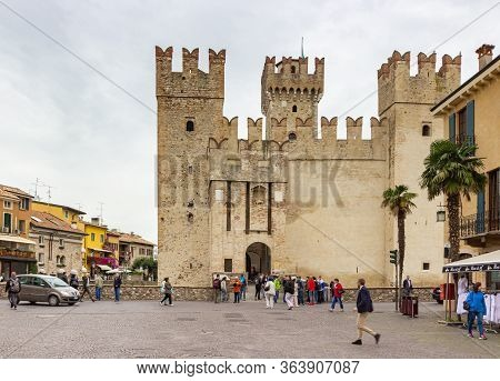 Sirmione, Italy - October 01, 2015 : Castello Scaligero Fortress On Lake Garda. Tourists Walk Around