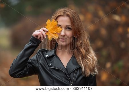 Portrait Of Smiling Redhead Woman With Yellow Leaf With Long Curly Hair On Blurred Autumn Background