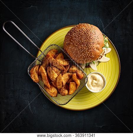 Vegetarian Burger And Golden Potatoes With Garlic Sauce On Dark Background