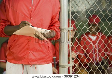Midsection of a man holding the scorecard of his team with players sitting in background