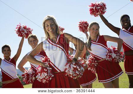 Portrait of cheerleaders with pom-pom on field