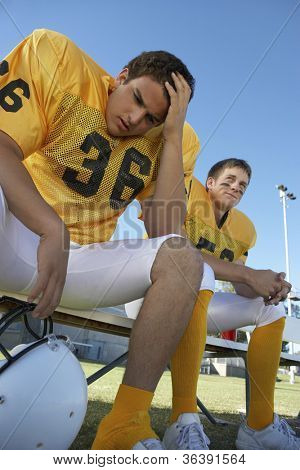 Low angle view of a tense american football player sitting with teammate on bench