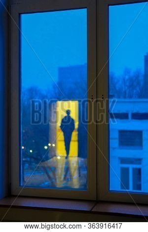 the image in the window of the illuminated silhouette of a man