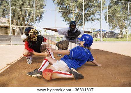Softball player sliding into base with baseman and umpire