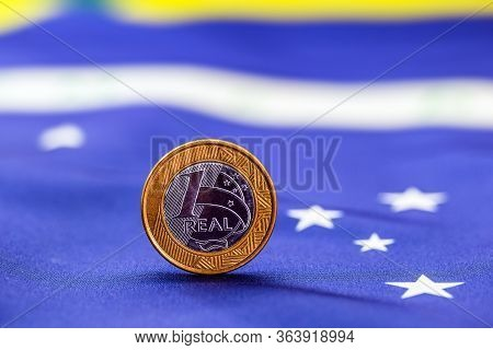 One Brazilian Real Coin With Brazil Flag In The Background. Brazil Economy Concept