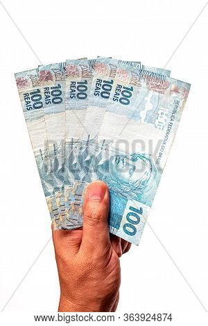 100 Reais Bills From Brazil, Held By Male Hand On Isolated White Background. Banknotes Of One Hundre