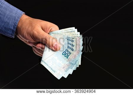 Hand Holding Several Hundred Reais Bills From Brazil, On Isolated Black Background. Emergency Govern